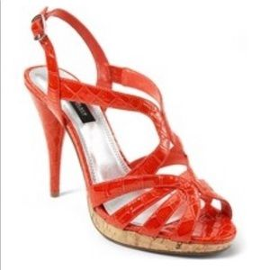 Red faux patent leather patent strappy heel.